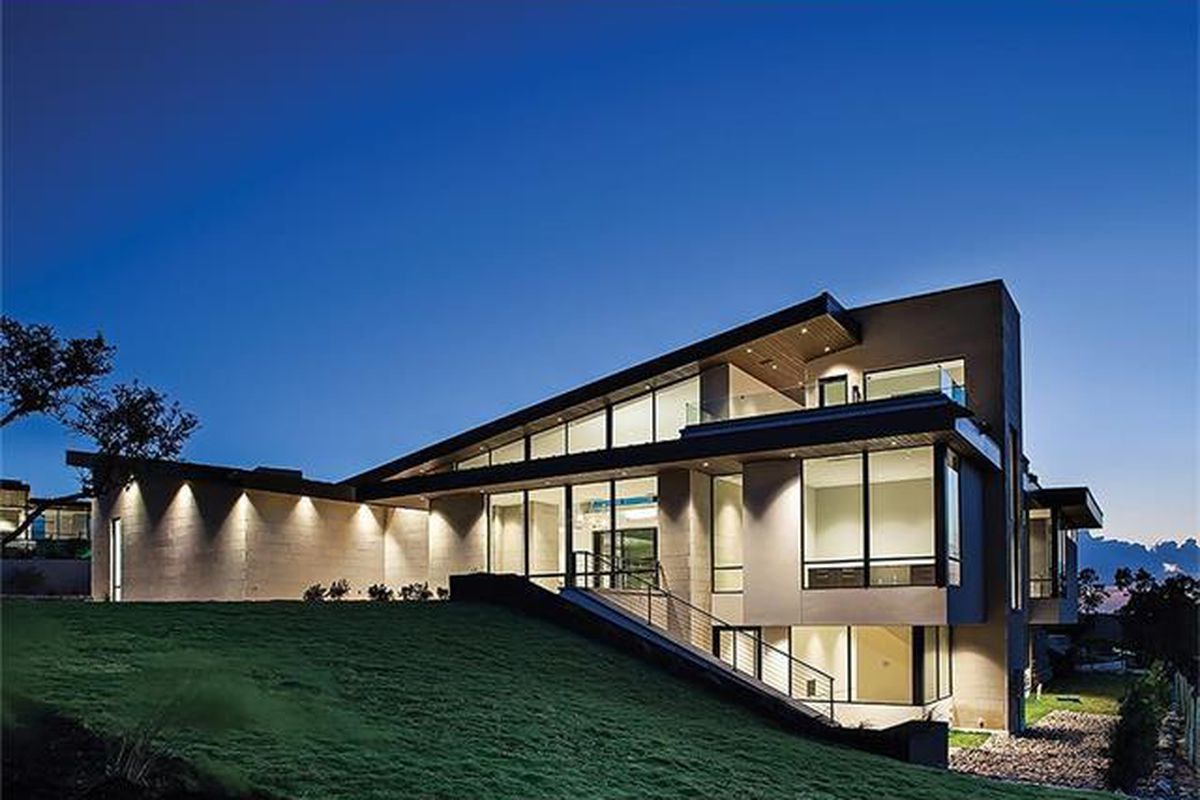 Large contemporary at dusk with levels on hillside