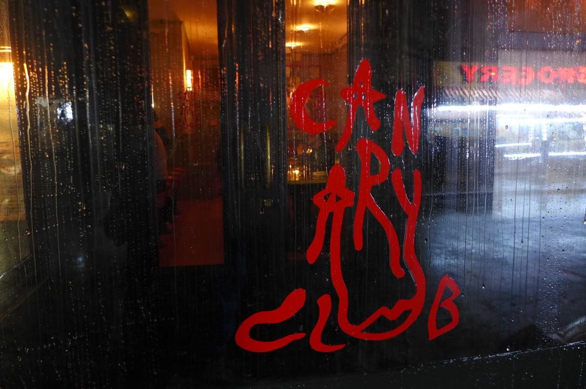 A swirl of red paint says Canary Club after you look at it long enough.