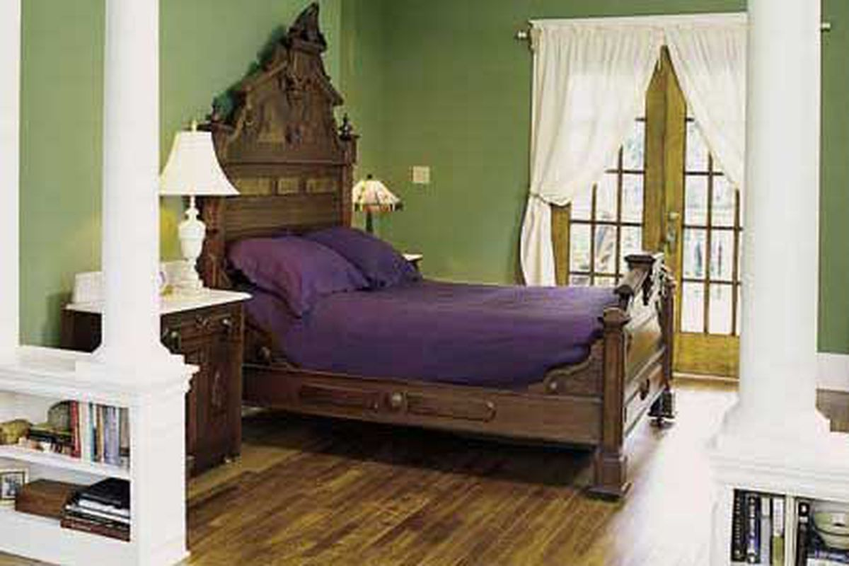 Bedroom with green walls and wooden bed frame.
