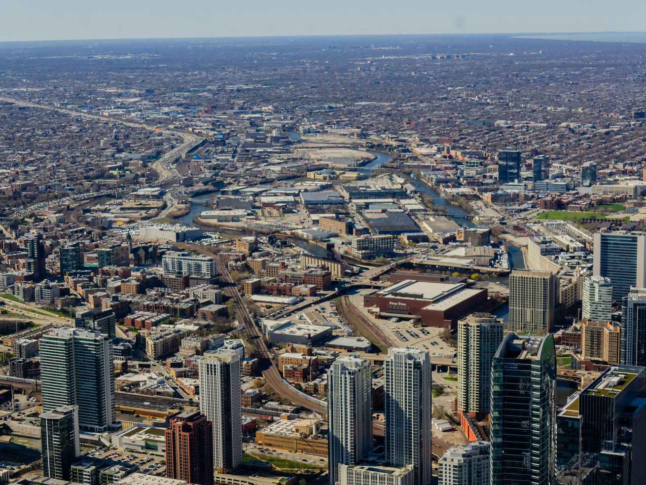 A bird's eye view of Chicago shows the confluence of the river, a few towers on the west end of the Loop, and smaller buildings of neighborhoods.
