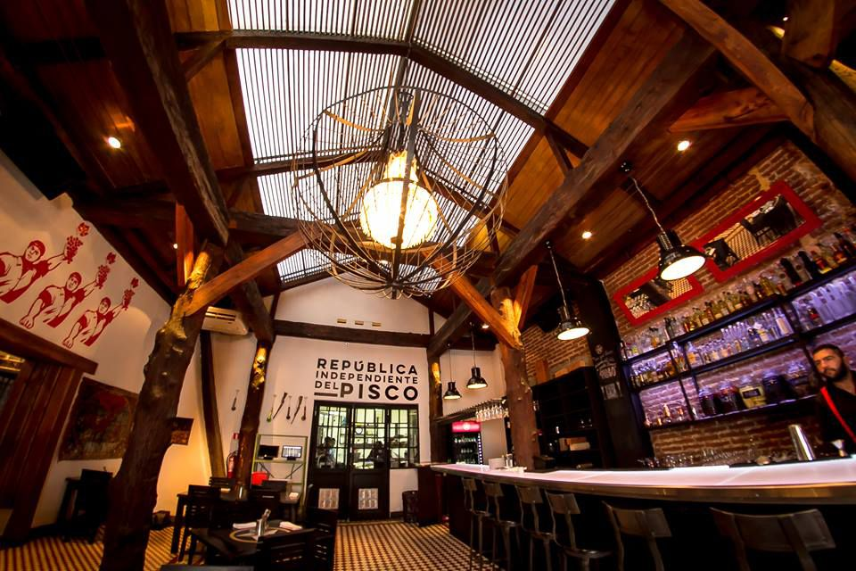 A low angle shot looking up at an airy bar topped with a large skylight. The space also includes a caged pendant light in the center of the photo, tiled flooring, a few tables, tall backlit shelves and a bartender at work.