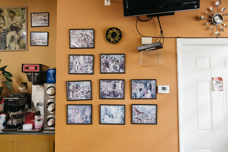 An orange wall with a series of framed photos next to a beverage machine.