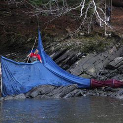 In this photo made Thursday, March 23, 2012, elver fishermen set up a fyke net on the bank of river in southern Maine. The baby eels are fetching the fishermen more than $2,000 per pound this year. They are sold to the Asian market where they are grown to adults.