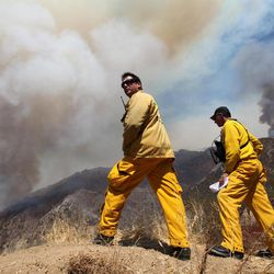 Los Angeles County Fire Department firefighters, Mitch Brookhyser, left, and Denis Cross survey the Williams Fire burning in the San Gabriel Mountains in the Angeles National Forest near Glendora, Calif., Tuesday, Sept. 4, 2012. A 3,600-acre brush fire continued to burn in the Angeles National Forest about 25 miles northeast of downtown Los Angeles on Tuesday as crews worked in the steep, rugged terrain to bring the blaze under control. The fire was about 15 percent contained and officials said it could take a week to bring it under control.
