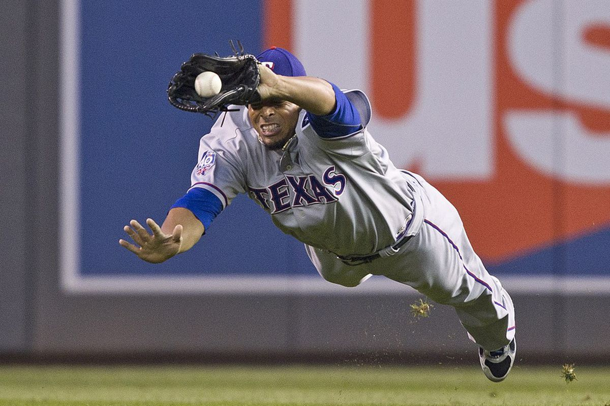 Apr 13, 2012; Minneapolis, MN, USA: Texas Rangers right fielder Nelson Cruz (17) dives to catch a fly ball hit by Minnesota Twins shortstop Jamey Carroll (not pictured) in the first inning at Target Field. Mandatory Credit: Jesse Johnson-US PRESSWIRE