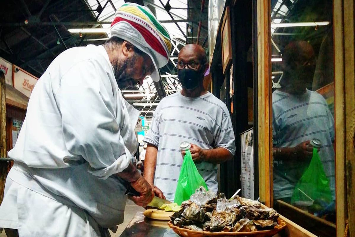 Christopher preparing oysters at The Lone Fisherman in Tooting Market, with a customer waiting