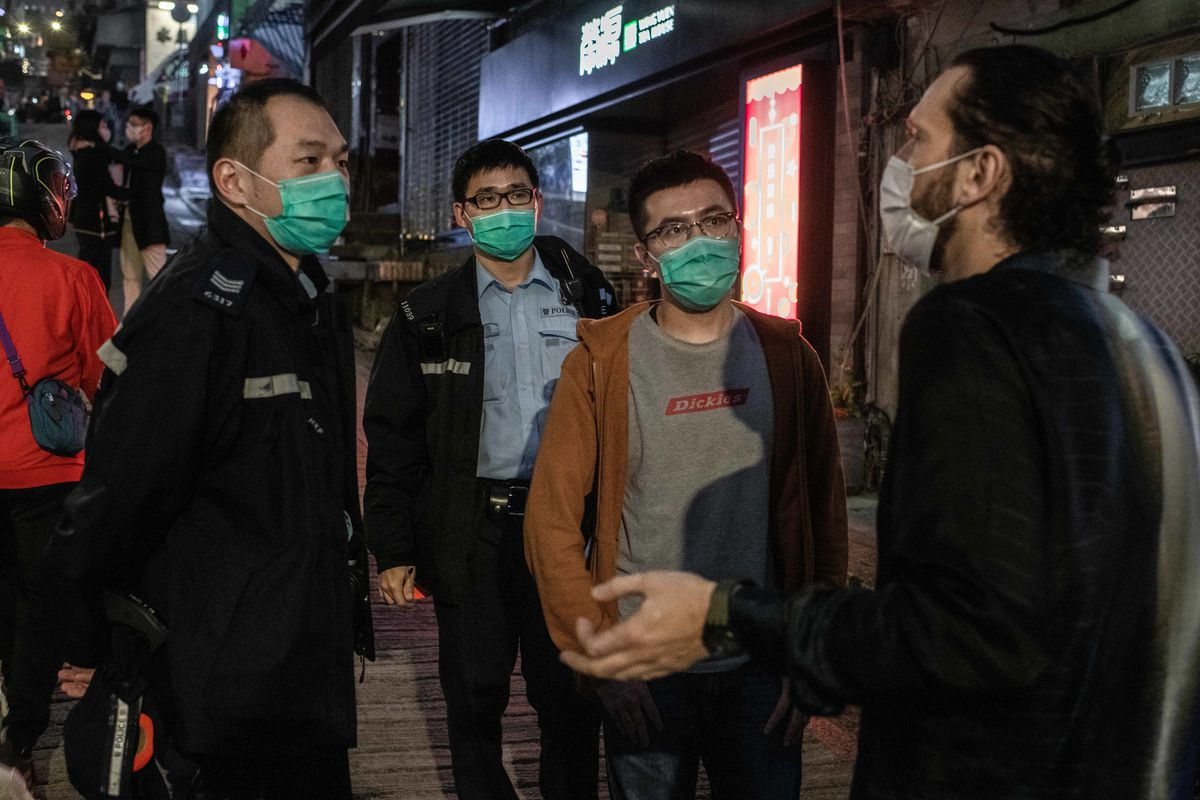 Police agents speak with the manager of a pub in Soho, Hong Kong