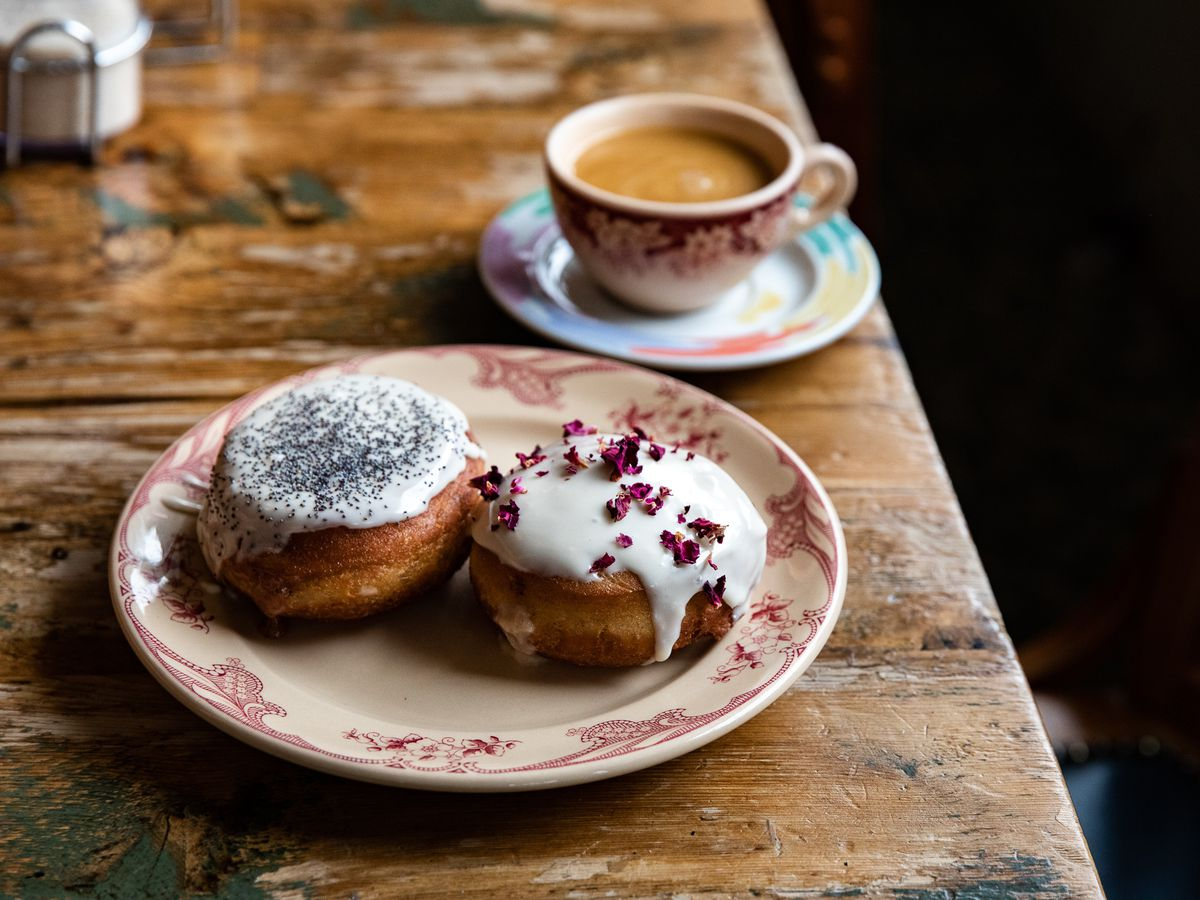 Two paczki covered with white icing and sprinkles of poppy seed and rose petals.