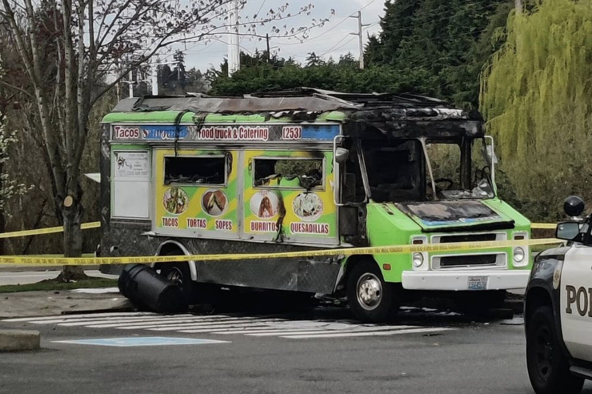 A food truck damaged by fire sits behind yellow police caution tape, with a police vehicle parked to the right.
