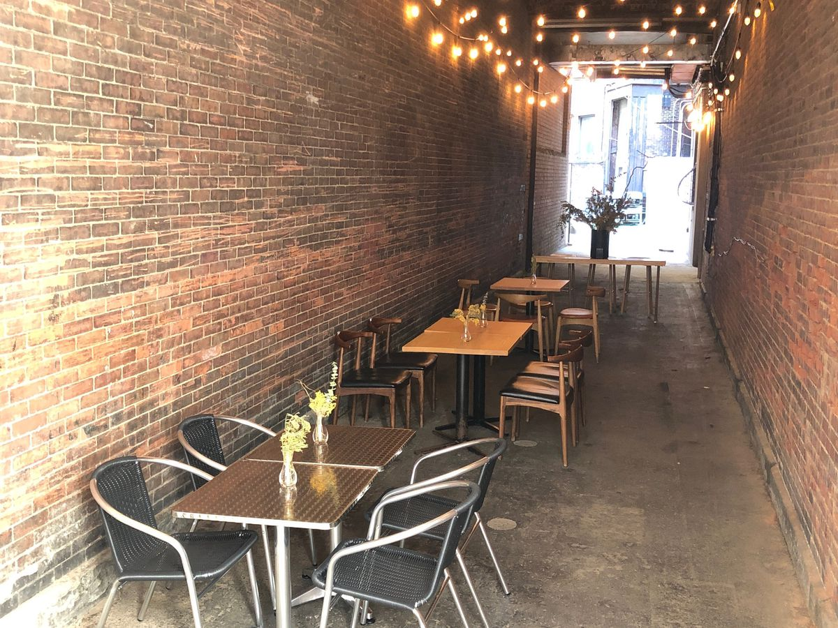 Tables and chairs set up in a covered brick alleyway