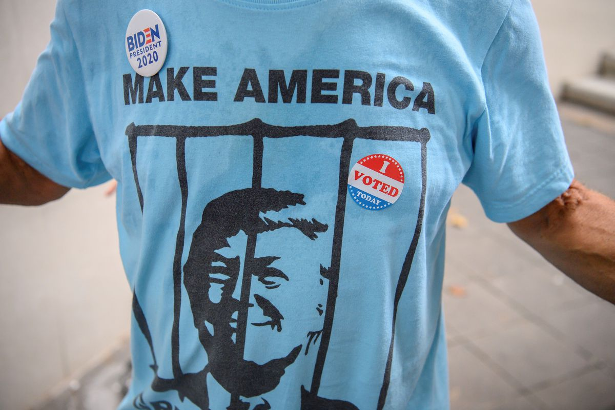 A US citizen in Thailand wears a blue shirt showing Trump behind bars and a Biden for President pin to drop off his ballot at the embassy in Bangkok.