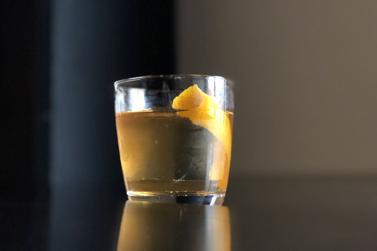 A lowball glass with a huge chunk of clear ice, an orange peel garnish