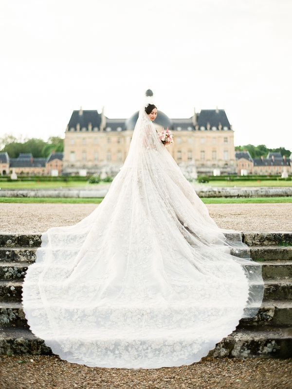 A bride in her wedding dress outside the French château where her wedding was held.