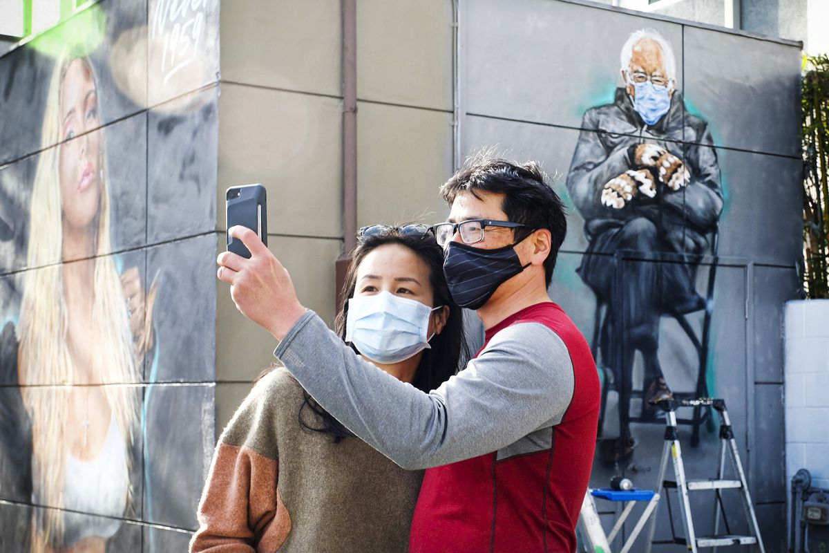 Two people taking a selfie in front of a mural of Sen. Bernie Sanders.