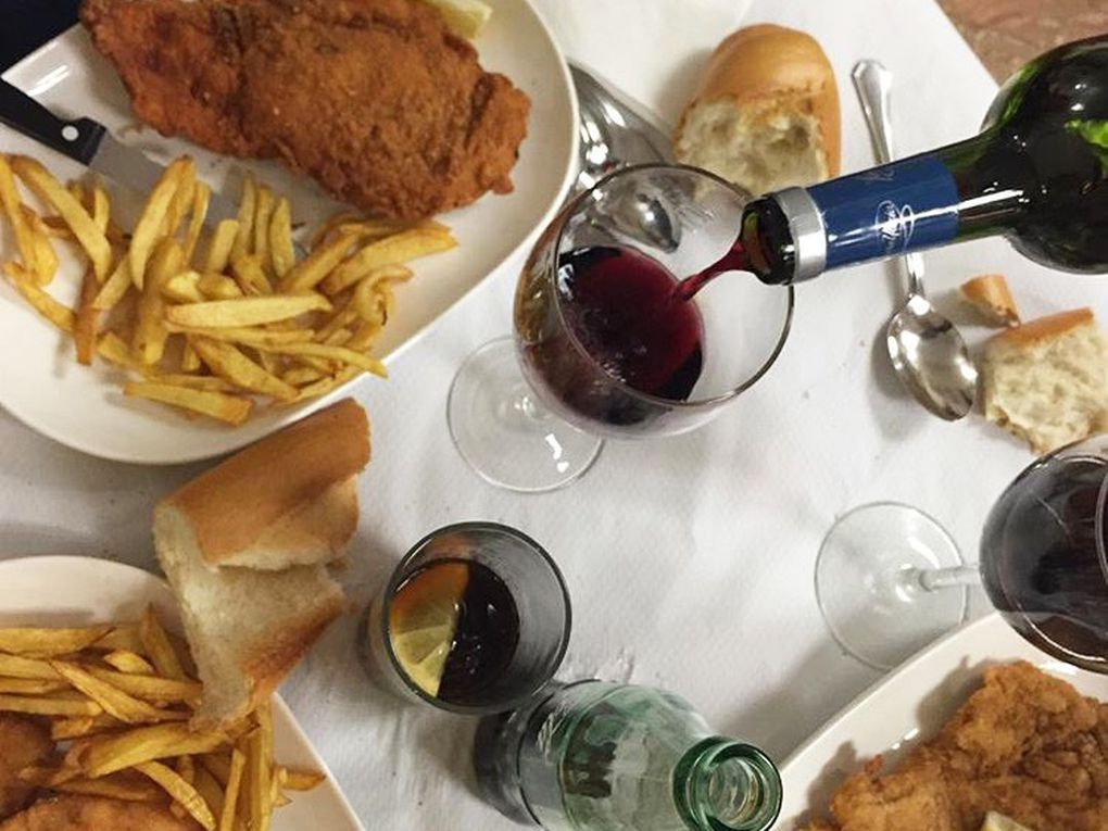 A full table of dishes, including a fried cutlet, french fries, chunks of bread and red wine glasses.
