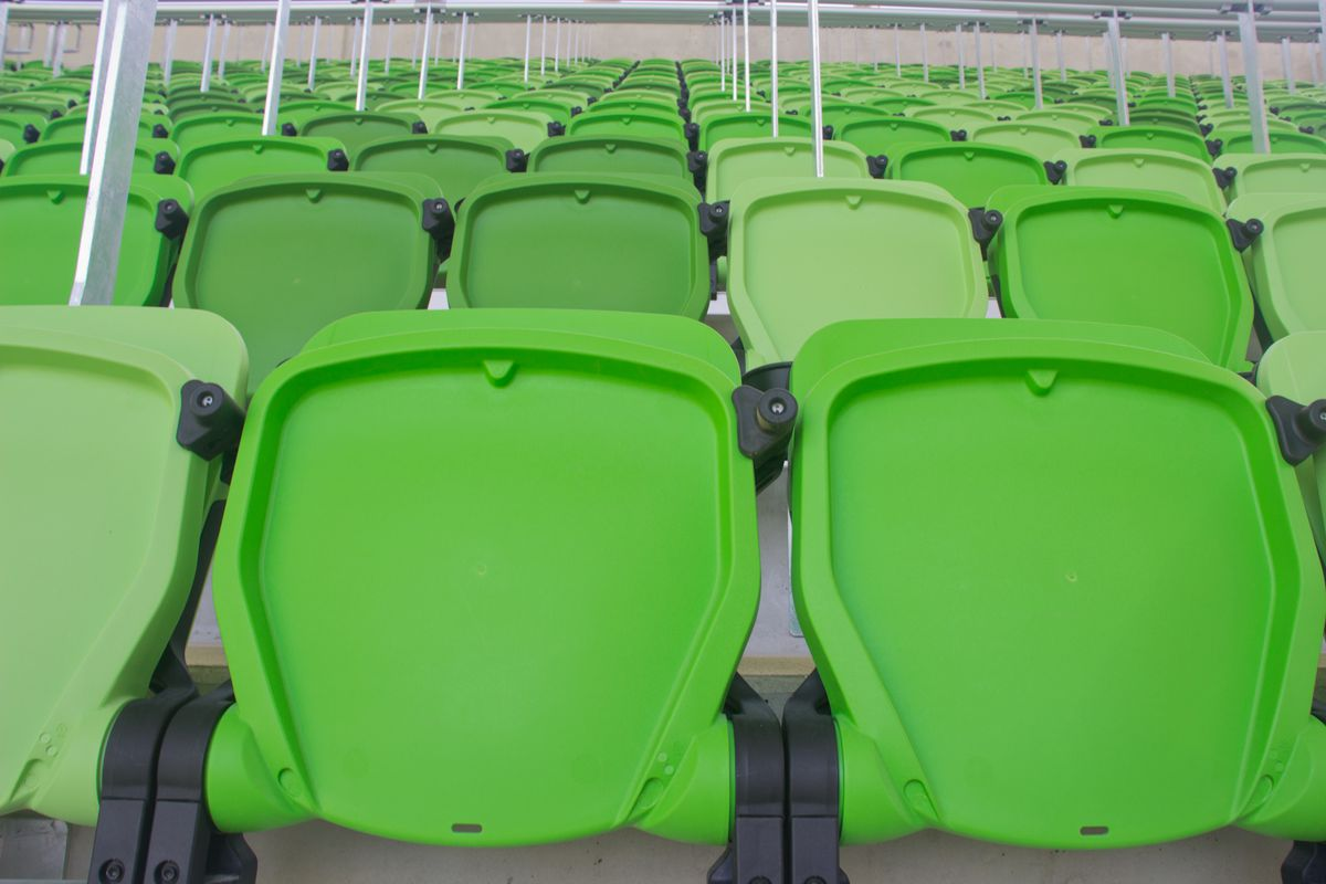 Folded-up stadium seats in varying shades of greeen