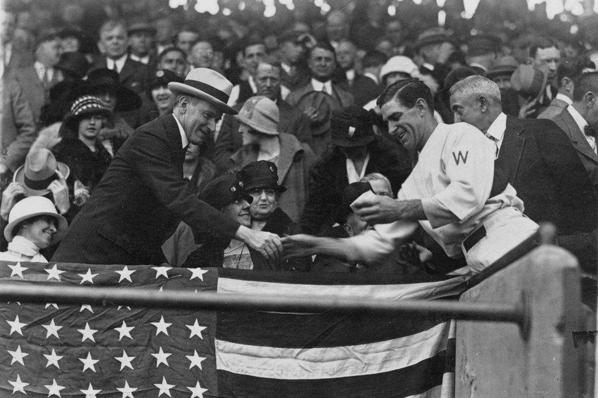 """Washington Senators manager Stanley """"Bucky"""" Harris, in the grandstand, presents President Calvin Coolidge (at left) with the baseball used to open the 1924 World Series."""