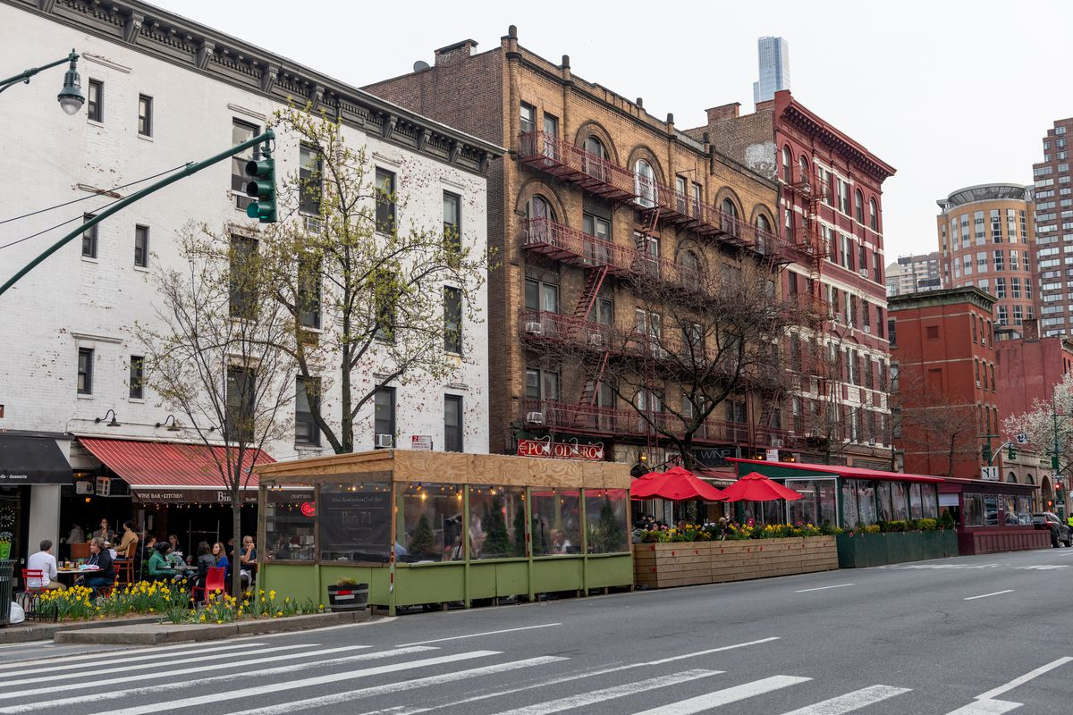People fill outdoor dining structures lining a street on the Upper West Side amid the coronavirus pandemic on April 10, 2021 in New York City.
