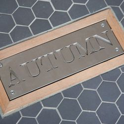 A plaque on the floor by the door announces the seasonal muse of the moment for AQ's decor and menu.