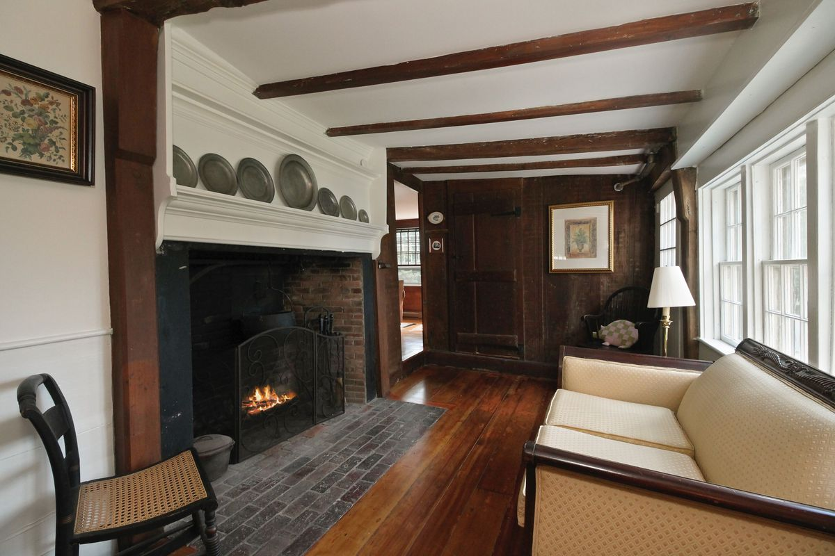 A colonial parlor consists of wood pine floors, a large historic fireplace on the left, white walls, exposed beams, and a simple chair and couch.
