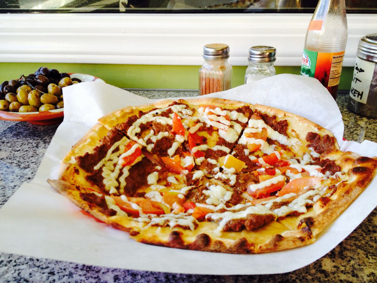 Middle Eastern flatbread drizzled with white sauce and a variety of toppings