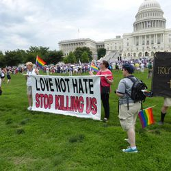 """As a rally for the 2014 """"March for Marriage"""" begins, six protesters hold a banner claiming supporters of traditional marriage are """"killing us."""""""