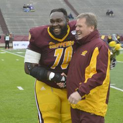 Oge Udeogu shakes hands and shares a laugh with Jim McElwain during Senior Day ceremonies.