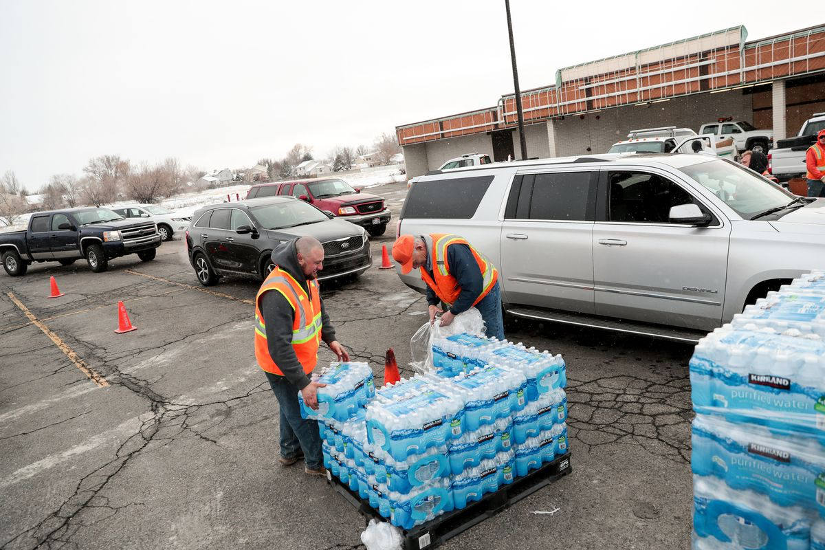 FILE - Sandy city employees Taylor Vick and Mike Fox distribute water to residents at a staging area on 700 East in Sandy on Saturday, Feb. 16, 2019. Nearly 3,000 homes in Sandy were given the OK by Sandy city officials on Sunday to drink water out of the