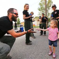 Jonathon Hodgkiss of Lone Peak Engines out  of Utah accepts a doughnut and lemonade from Skylee Hatch as fire crews return from fighting the Brian Head Fire near the town of Panguitch on Tuesday, June 27, 2017.