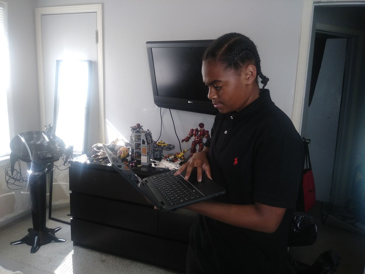 King Bethel standing in his room beside his dresser and music stand working on a laptop.