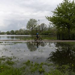 A young boy rides his bike past a large puddle at Humboldt Park, Monday, May 18, 2020. Much of the Chicago area experienced flooding after rain showers over the weekend.