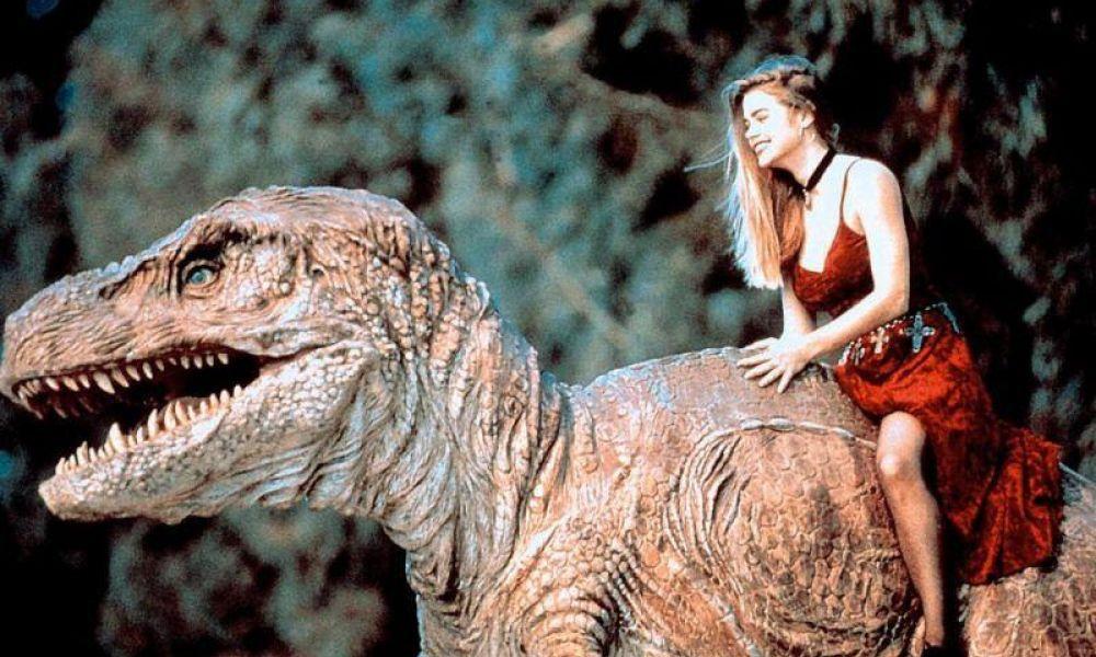 a girl in a prom dress rides a t-rex