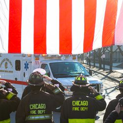 Chicago Fire Fighters salute as the procession for a off duty Chicago Police Officer who was fatally shot inside his car in the River North neighborhood arrives at the Cook County Medical Examiners Office, Saturday, March 23, 2019, in Chicago.   Tyler LaRiviere/Sun-Times