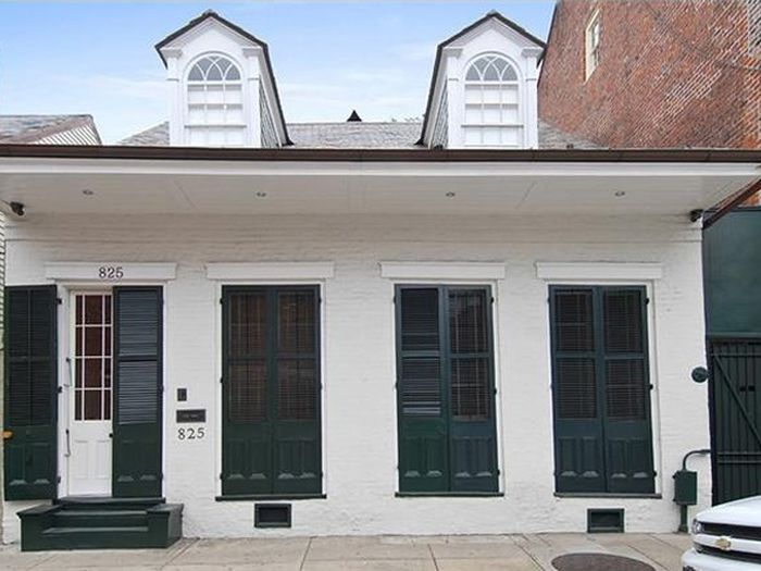 The exterior of 825 Dumaine Street. The facade is white and there are black shutters.