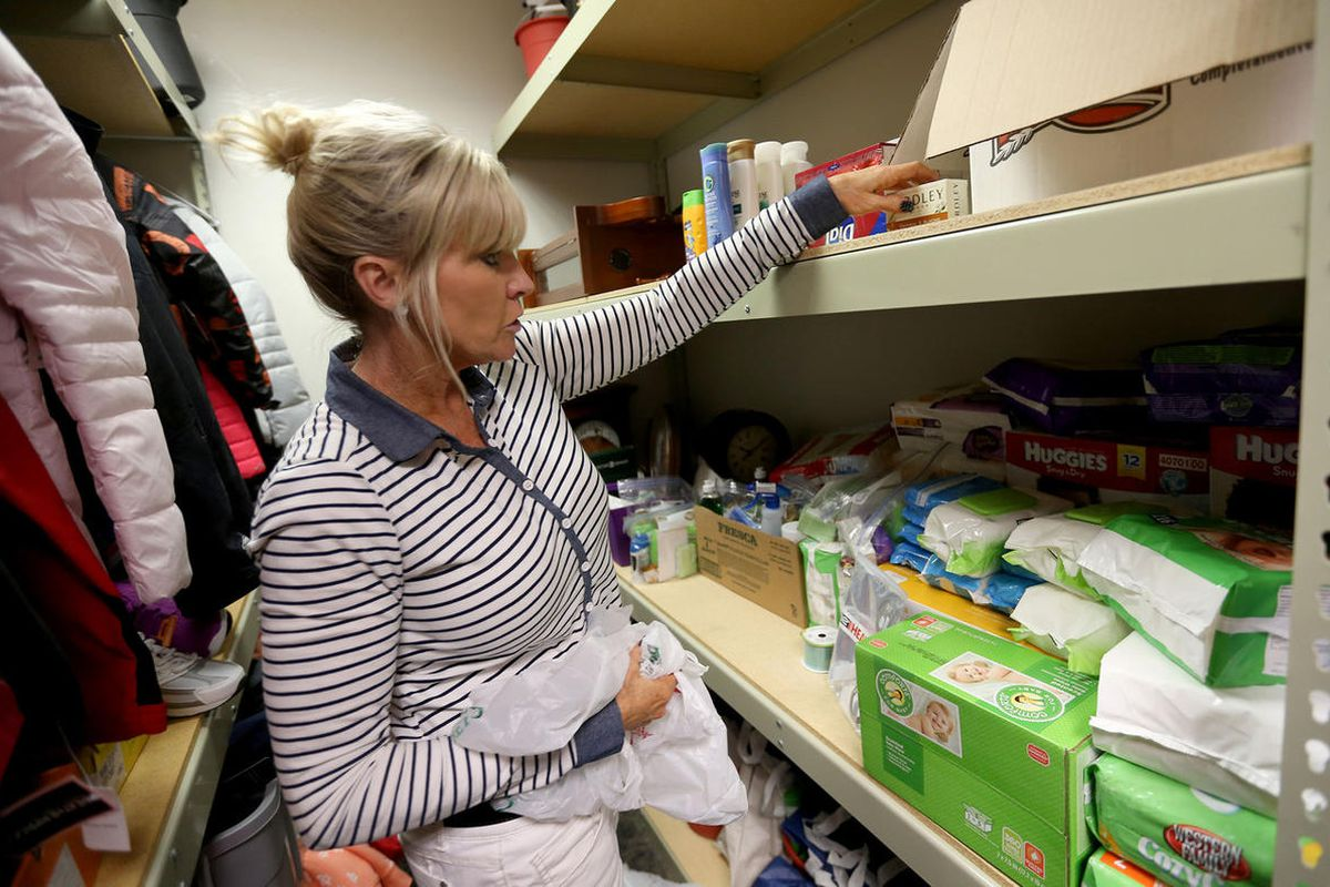 FILE - Deb Coffey, Development Director for the Granite Education Foundation, sorts donated hygiene products at Granite Refugee Center in Salt Lake City on Monday, March 28,  2016.  The First Presidency of The Church of Jesus Christ of Latter-day Saints i