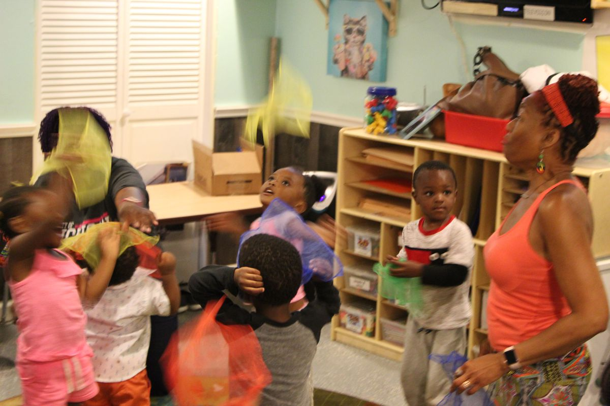 Students play with colored scarves as part of an interactive lesson at Jill's Creative Learning, a child care center in Detroit's Brightmoor neighborhood.