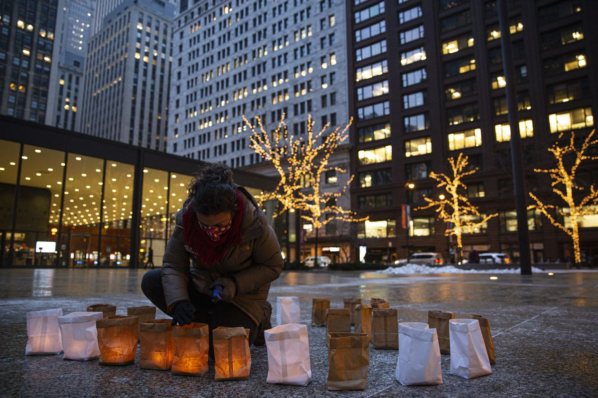 Cate Readling lights candles Tuesday at Federal Plaza in remembrance and of Nickolas Lee, an inmate who died of COVID-19 at the Cook County Jail.