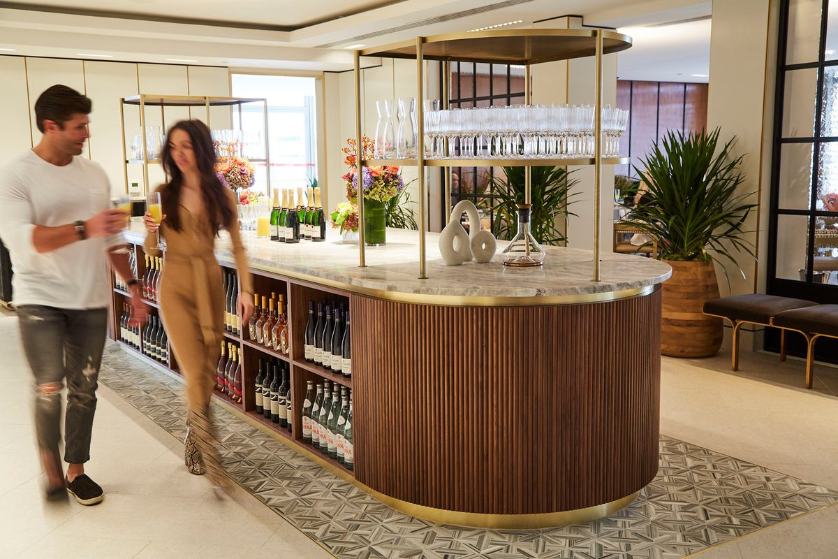 two people walking past a wine bar inside a hotel. their images are blurry, as if it is a time-lapse photo