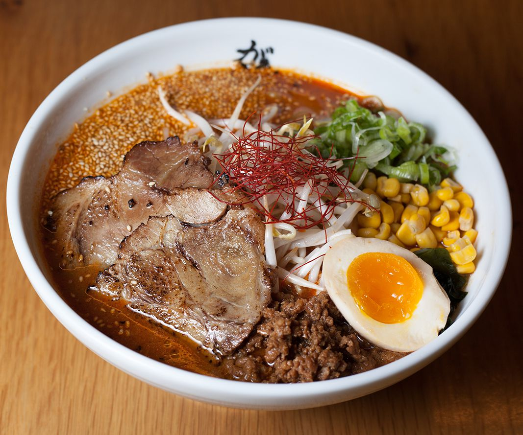 A large bowl of ramen shows an oily broth, a slice of meat, and toppings of a soft-boiled egg and vegetables