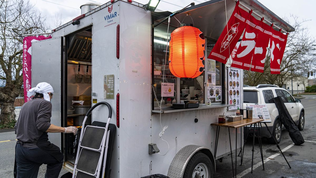 A man wearing a white head scarf enters a small mobile food cart with red flags displaying Japanese characters and an orange glowing paper lantern out front.