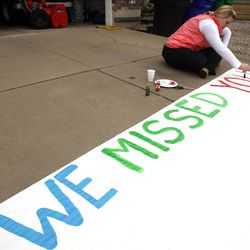 Brooke Taylor paints a sign prior to Clara Lewis' return home from the hospital in Centerville  Thursday, Dec. 29, 2011. Clara Lewis was severely injured in mid-November when her vehicle was struck by a FrontRunner train in Kaysville at a crossing.