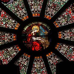 St. Cecilia, patroness of music, is depicted in the center of the rose window of the Cathedral of the Madeleine.