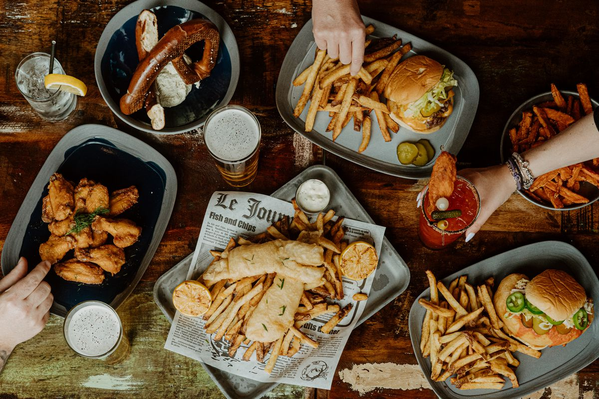 table covered in dishes with chicken wings, burgers and fries