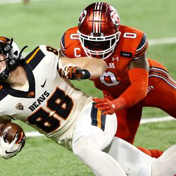 Utah Utes linebacker Devin Lloyd (0) pushes Oregon State Beavers tight end Luke Musgrave (88) out of bounds after a catch and run as Utah and Oregon State play a college football game at Rice Eccles stadium in Salt Lake City on Sunday, Dec. 6, 2020. Utah won 30-24.
