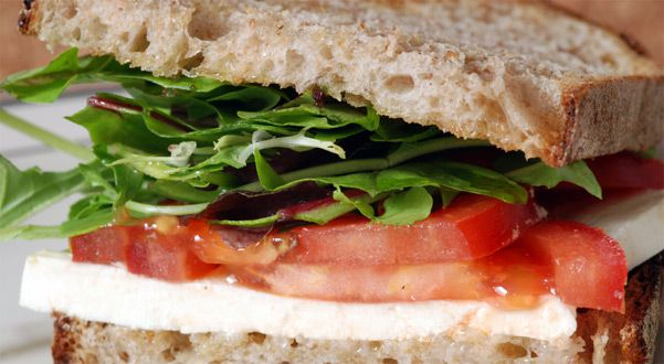 Tomato-mozzarella sandwich with lettuce on wheat bread