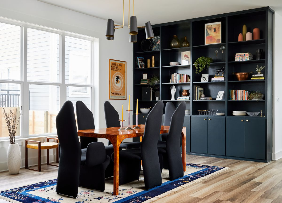 A bright dining room with high ceilings has a wall of black bookshelves filled with decor, plants, and books. At the center of the room is a wood dining table surrounded by sculptural black chairs; a bright art deco rug sits underneath.