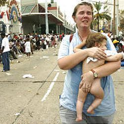Lee Bemboom struggles to carry her 11-month-old baby boy, Jahon Bemboom, as she searches for help Thursday among thousands of people gathered inside and outside the Convention Center in New Orleans to wait for buses in the aftermath of Hurricane Katrina. She was trying to leave the Convention Center area to search for help elsewhere.