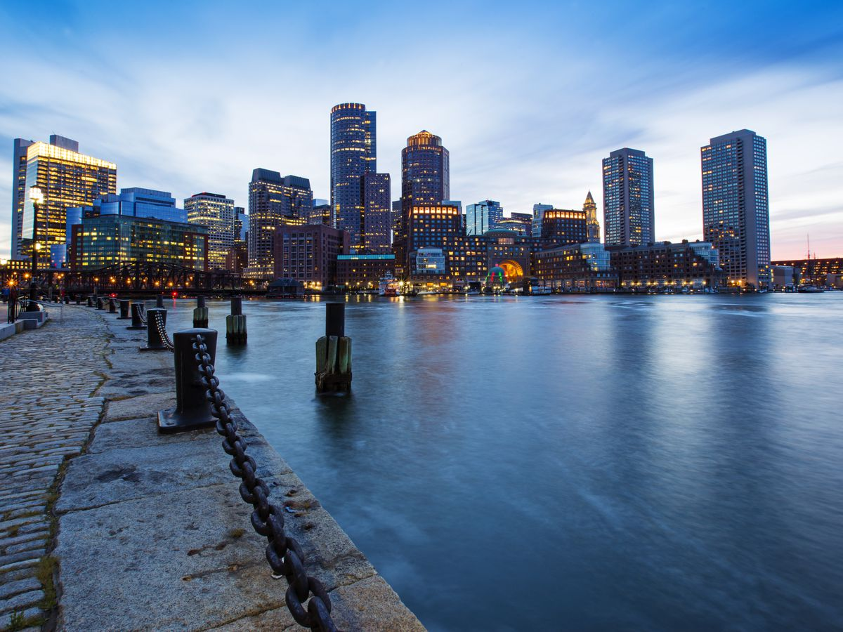 A walkway next to Boston Harbor with the city's skyscrapers lighting up at dusk.