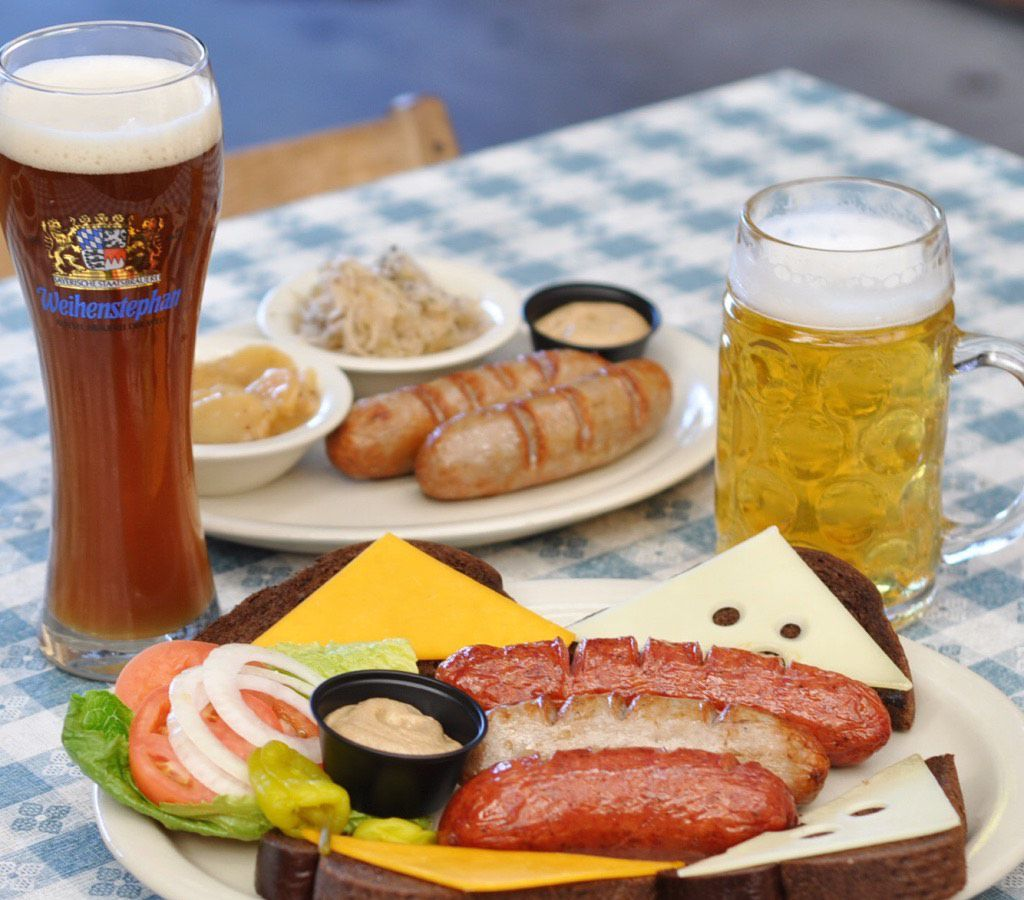A platter of sausages, rye bread and mustard on a picnic table with two beers