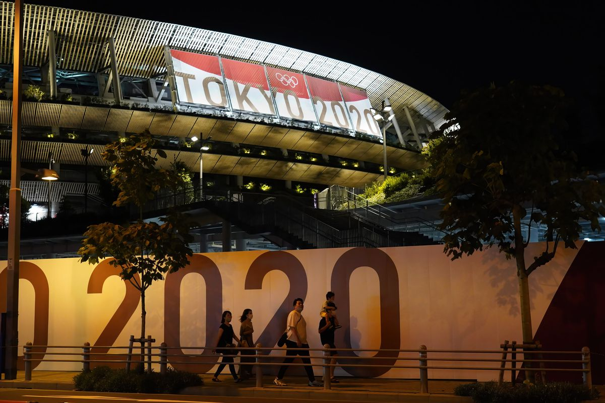 People walk past Tokyo Olympic Stadium on the eve of the opening ceremony. With just one day until the Olympics opening ceremony, Tokyo confirms 1,979 new coronavirus infections. The total number of cases in Tokyo now stands at 195,041.
